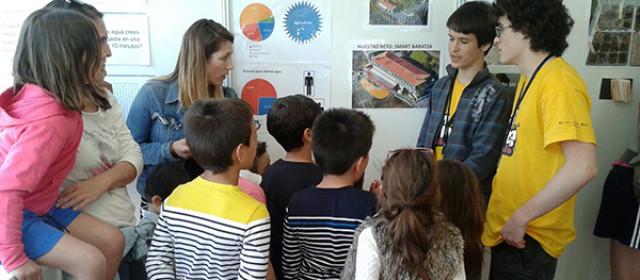 En la fotografía unos niños reciben explicaciones sobre el proyecto de Overclock